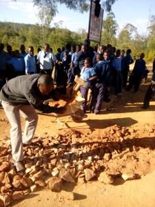 students repairing gravel road.